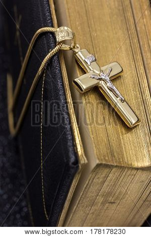 Beautiful golden crucifix and vintage Bible with gilded pages