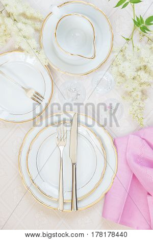 Top view of the beautifully decorated table with white plates crystal glasses pink linen napkin cutlery and flowers on luxurious tablecloths