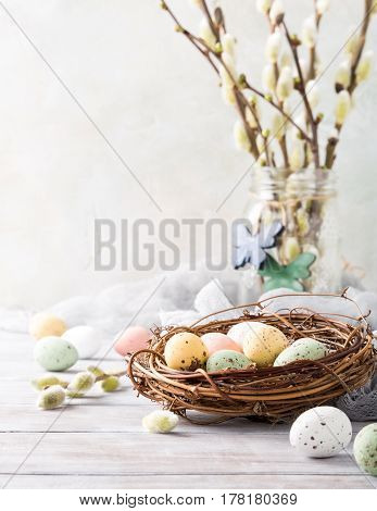 Easter composition of colorful quail eggs in the nest on the light wooden background. Holiday concept with copy space.