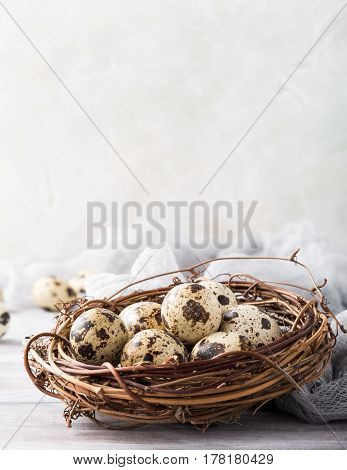 Easter composition of quail eggs in the nest on the light wooden background. Holiday concept with copy space.