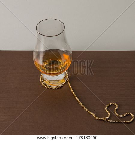 A Single Malt Whiskey Glass, On A Brown Plane, With A Gold Chain