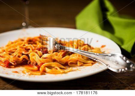 Closeup of half-eaten tagliatelle pasta with bolognese ragu over a rustic table