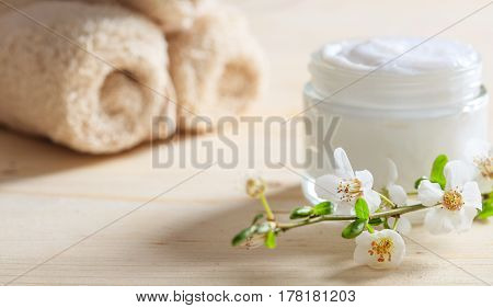 Moisturizing Cream And Almond Blooms On Wooden Background