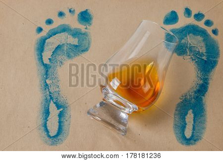Overturned Glass Of Single Malt Whiskey, Gray Paper With Blue Footprints