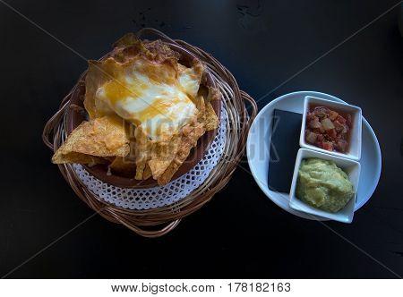 Nachos with cheese salsa and guacamole on dark background.