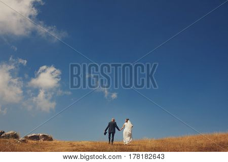 Bride and groom walking in the hills against the blue sky
