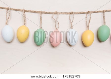 Colorful Easter eggs hanging on rope over wooden background.