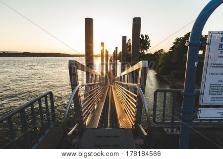 Metal ramp with railings leading down to the dock of the Columbia River in Vancouver Washington USA. Sunset in the distance.