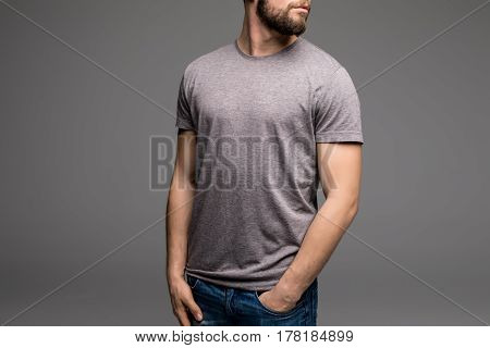A Man In A Grey T-shirt And Denims Holds His Hands In Pockets.