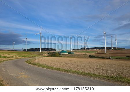 Different fermenters of a biogas plant with windmill in the background.Biogas plant with wind turbine.