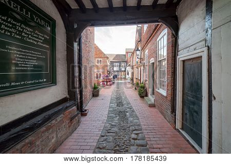 Farnham, UK. 25th March 2017, The entrance to Borelli yard which is an 18th century courtyard providing shops and retail establishments just off the High Street in Farnham, Surrey.