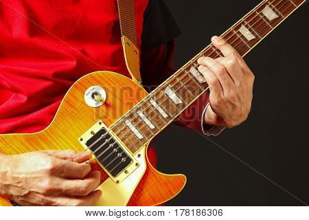 Rock guitarist playing the electric guitar on a dark background