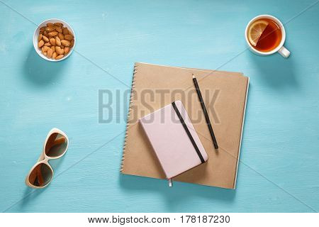 Flat composition of sketch book, pink diary, pensil, sunglasses and saucer with almonds.