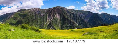 From the lawn with flowers opens a panoramic view of the rocky mountains green meadows and cloudy sky. Upper Svaneti Georgia Europe. Happy lifestyle. Beautiful universe.