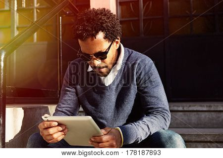 Young black man siting on street, looking around, reading, working on laptop computer. Instagram effect.