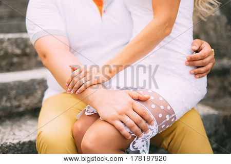 Girlfriend sitting in the lap. A loving couple is sitting on the stairs in Montenegro.