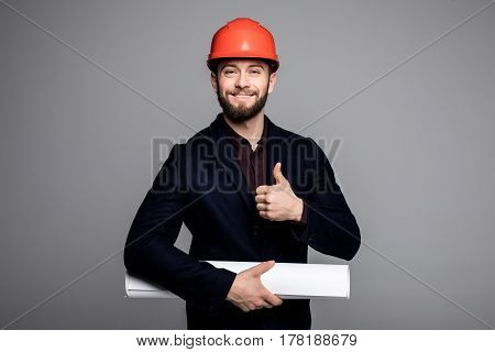 Portrait Of A Smiling Architect In Hard Hat With Blueprint Gesturing Thumbs Up On Grey