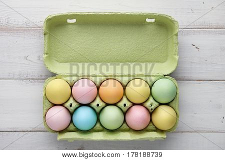 Colorful easter eggs packaging on white wooden planks