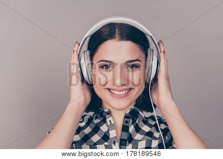 A Horizontal Portrait Of  Happy Young Girl In Checkered Shirt And Headphones Getting Pleasure From L