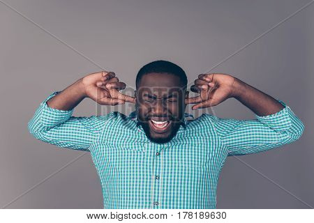 Portrait Of Furious Afroamerican Man Covering His Ears And Screaming