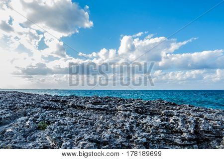 A simple tropical beach made of rock with clouds and the ocean in the background. New Providence Island, Nassau, Bahamas.