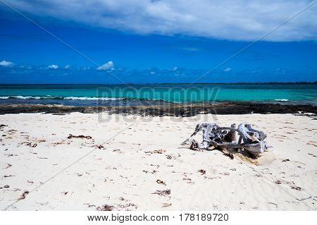 A beautiful tropical beach with rocks, clouds, and driftwood. New Providence Island, Nassau, Bahamas.