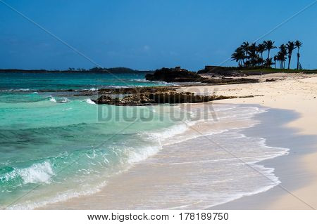 The tip of a beautiful tropical beach with rocks, palm trees, and waves. New Providence Island, Nassau, Bahamas.