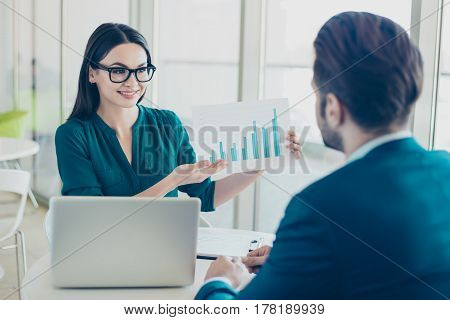 Young Cute Businesswoman In Spectacles Demonstrating Graph To Her Colleague