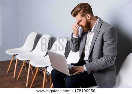 Horizontal Portrait Of Young Overworked Handsome Manager Having Terrible Headache At Work