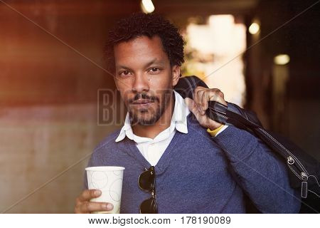 Portrait of a cool travel black guy walking with coffee in white cup.