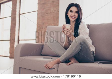 Portrait Of Beautiful Young Woman Sitting On Sofa At Home With Cup Gf Tea Near Big Window, Crossing