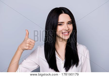 Portrait Of Beautiful Cute Young  Woman With Toothy Smile And Black Hair Showing  Thumb Up Sign With