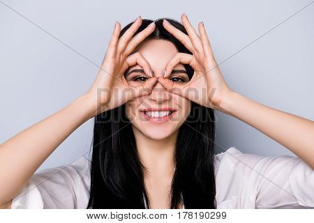 Young Cheerful Laughing Woman Having Fun And Making Binoculars Using Her Hands Isolated On Gray Back