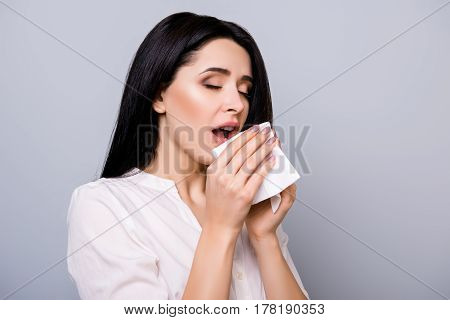 Horizontal Portrait Of Young Sick Woman Sneezing In Napkin