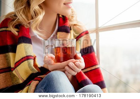 Close up photo cheerful happy woman holding cup of tea and sitting on windowsill