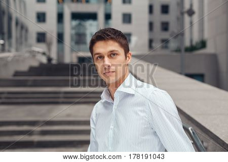 Portrait of handsome business man smiling, outside modern office building block.