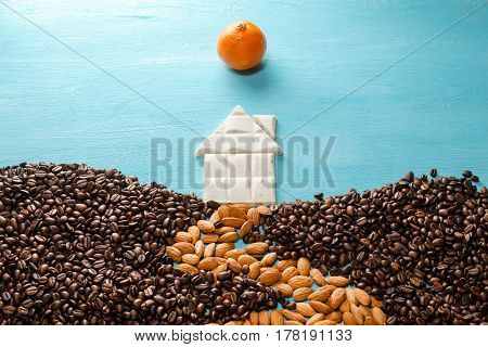 The house from white chocolate, the earth from coffee grains, the road from almonds, the sun from a citrus on blue background. Abstract symbols flat lay composition. Concept of realty, cosiness, comfort, happy family etc.