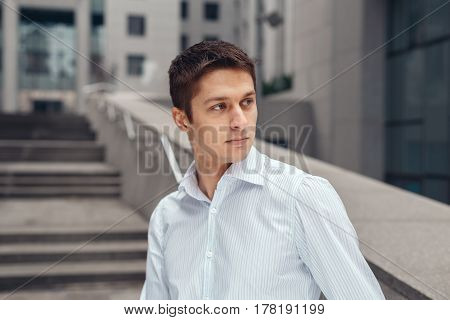 Cool business man leaning on urban wall outdoors. Young man in white shirt standing near the business center.