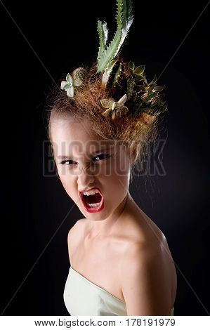 dark portrait of a Woman with cactus in her hair on a black background