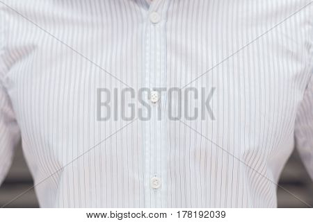 Close up part of a white business shirt on a man. Elegant beautiful shirt with buttons.