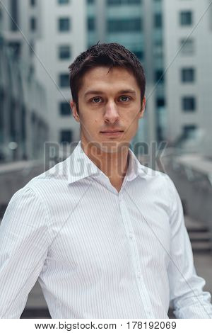 Smiling relaxed businessman standing in an urban square. Young business man looking at camera and posing.