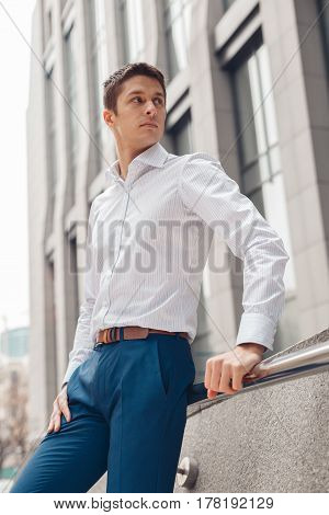 Young man dressed formal resting outdoors near business center. Serious young man in city.