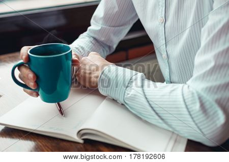 Close up businessman hands with cup of coffee. Coffee break in cafe.