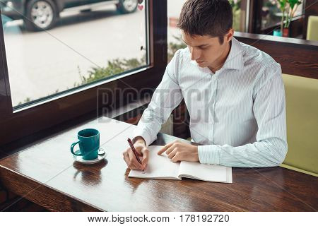 Handsome young businessman working and writing something in notebook. Confident young male with cup of coffee working outdoors.