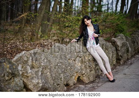 Brunette Gypsy Girl Posed Against Stones On Park. Model Wear On Leather Jacket And T-shirt With Orna