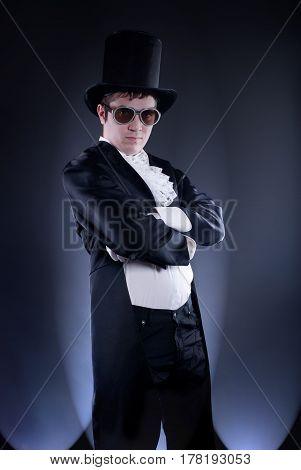 dark studio portrait of a man dressed as a magician