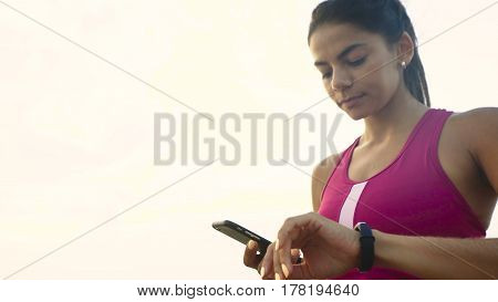 Serious young active woman checking miles on her fitness tracker