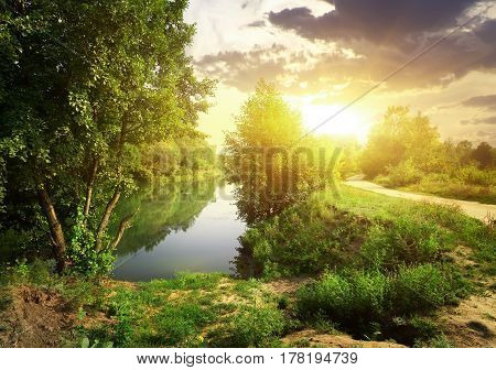Country road near river in sunny evening