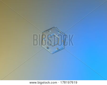 Macro photo of real snowflake: small snow crystal of hexagonal plate type with simple shape, relief central hexagon and six marks, resembling ancient runes, near to outer rim. Snowflake glitters on smooth gray - blue gradient background in cold light.