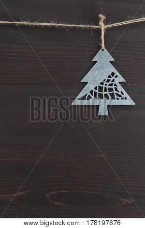 Offset Metal Pine Tree Ornament against wooden background